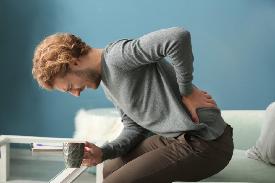 man touching lower back in pain