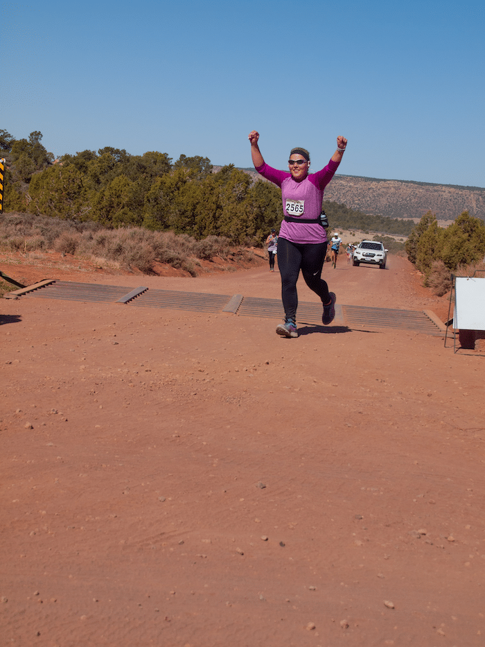 woman arms up finishing race